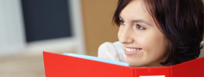 lächelnde frau im büro hält eine roten ordner vor sich